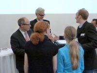 Senator Rabe überreicht Schülern des Grootmoor einen Gutschein für Brennstoffzellen zum Experimentieren.