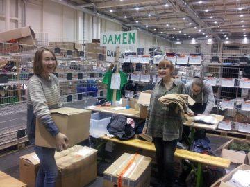 Mitglieder der Senegal-AG helfen beim Sortieren von Kleidung in der Kleiderkammer in den Messehallen.